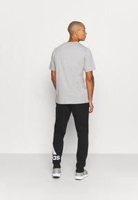 adidas Performance - ESSENTIALS - Tracksuit bottoms - black/white - 2