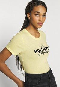 Hollister Co. - TECH CORE - Triko spotiskem - light soft yellow - 3