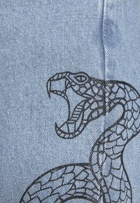 Milk it - SIDE SEAM SNAKE PRINT - Flared Jeans - light blue - 6