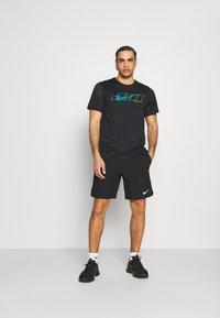 Nike Performance - T-shirt print - black/green abyss - 1