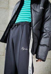 Pegador - WIDE TRACKPANTS UNISEX - Pantalon de survêtement - black/mint - 2