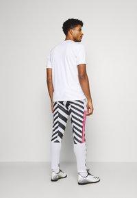 adidas Performance - MANCHESTER UNITED  - Tracksuit bottoms - white/black - 2