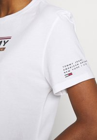 Tommy Jeans - TJW SLEEVE DETAIL LOGO TEE - T-shirts med print - white - 5