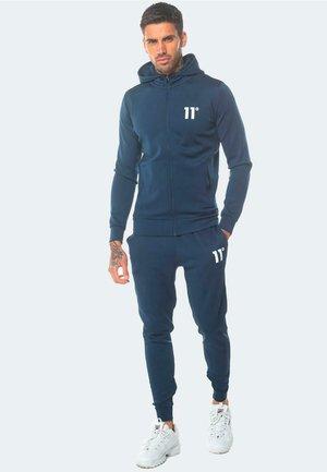 CORE POLY TRACK - Pantalones deportivos - insignia