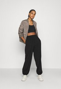 NA-KD - NA-KD X ZALANDO EXCLUSIVE - SPORTY FABRIC PANTS - Tracksuit bottoms - black - 1