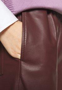 Marimekko - IHMETELLÄ TROUSERS - Leather trousers - wine red - 4