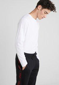 HUGO - DASCHKENT - Spodnie treningowe - black - 4