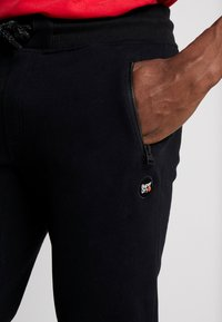 Superdry - COLLECTIVE - Tracksuit bottoms - black - 4