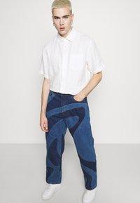 Jaded London - JADED MEN X CURLYFRYSFEED SWIRL CUT & SEW  - Bootcut jeans - dark blue - 3