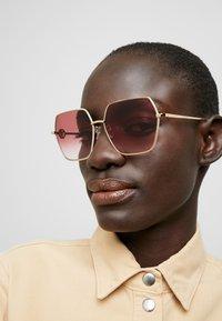 Alexander McQueen - Sunglasses - gold/red - 1