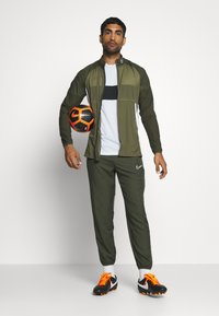 Nike Performance - DRY ACADEMY PANT - Tracksuit bottoms - cargo khaki/medium olive/white - 1