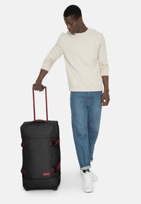 Eastpak - TRANVERZ M - Wheeled suitcase - blakoutstripred - 1
