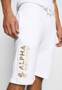 Alpha Industries - BASIC FOIL PRINT - Tracksuit bottoms - white/yellow gold - 4