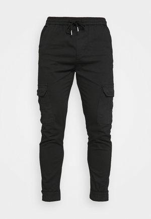 CREW - Reisitaskuhousut - black