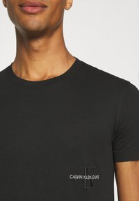 Calvin Klein Jeans - OFF PLACED ICONIC TEE UNISEX - T-shirt con stampa - black - 5