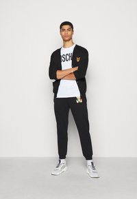 MOSCHINO - TROUSERS - Tracksuit bottoms - black - 1
