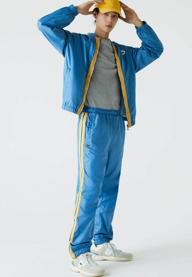 Pantalon de survêtement - blau / gelb / weiß / dunkelgrün