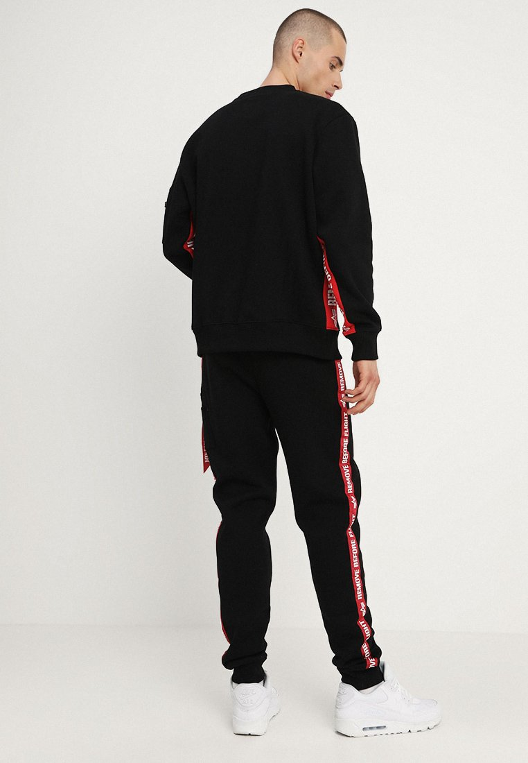 Alpha Industries JOGGER TAPE - Tracksuit bottoms - black NuAjj