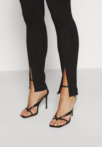 NA-KD - FRONT SLIT PANTS - Trousers - black - 6