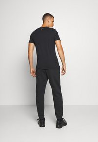 Reebok - CUFFED PANT - Pantalon de survêtement - black - 2