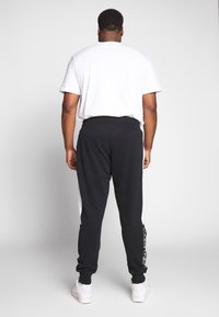 Calvin Klein - LOGO STRIPE  - Tracksuit bottoms - black - 2
