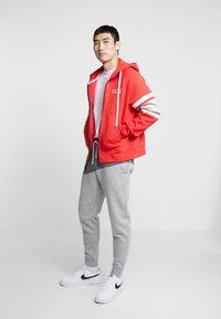 Nike Sportswear - Pantalon de survêtement - charcoal heathr/dark grey heather/university red - 1
