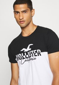 Hollister Co. - TECH LOGO SPLICING - Print T-shirt - black/white - 3