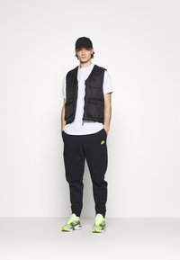 Nike Sportswear - Tracksuit bottoms - black/volt - 1
