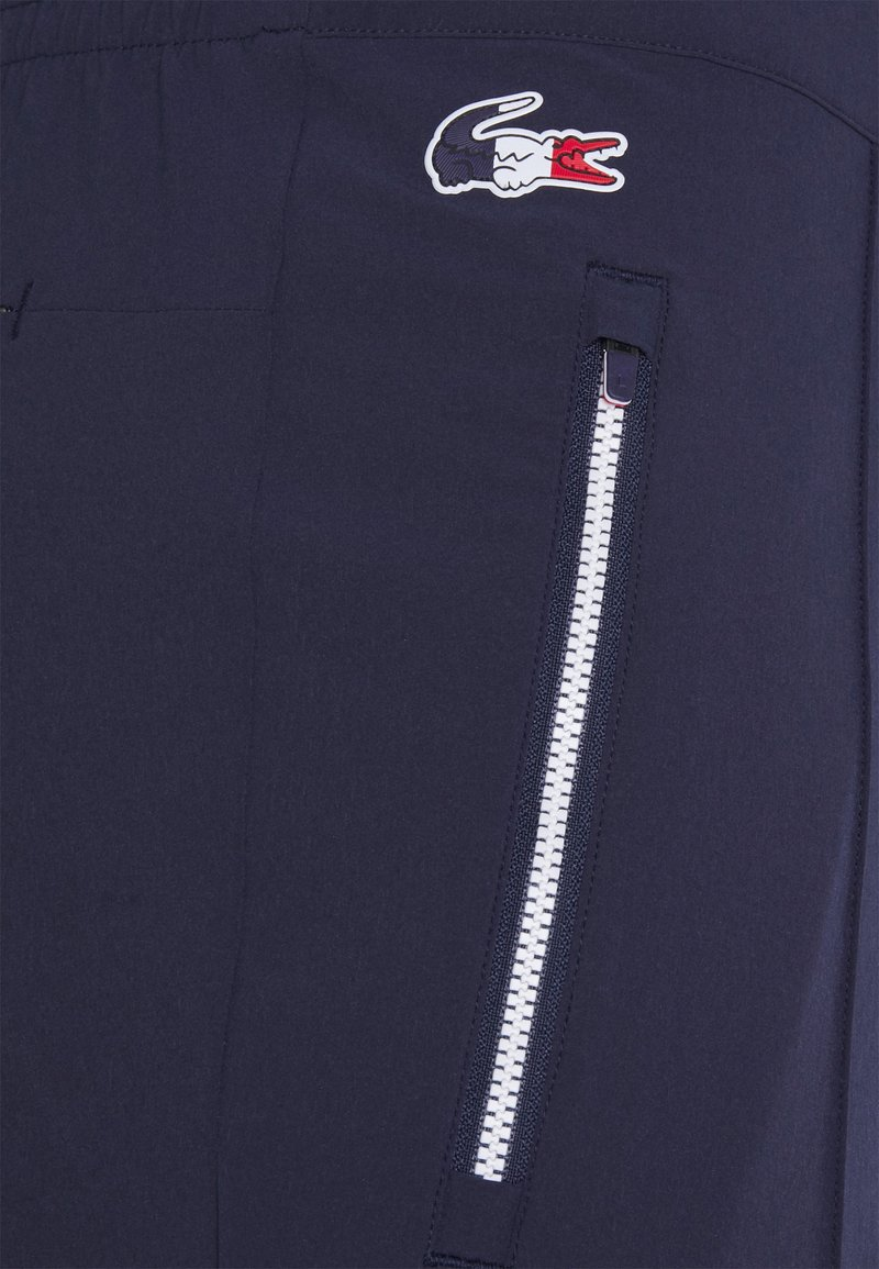 Lacoste Sport - OLYMP PANT - Tracksuit bottoms - navy blue/white