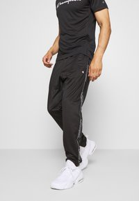 Champion - LEGACY TAPE CUFF PANTS - Tracksuit bottoms - black - 0