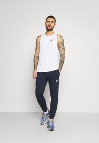 Nike Performance - PANT TAPER - Pantalon de survêtement - obsidian/white - 1
