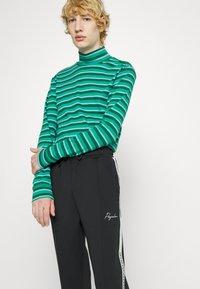 Pegador - WIDE TRACKPANTS UNISEX - Pantalon de survêtement - black/mint - 5