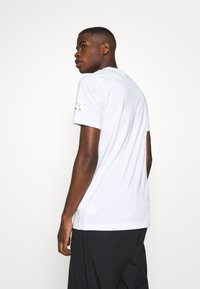 Puma - GRAPHIC TEE - Print T-shirt - white gold - 2
