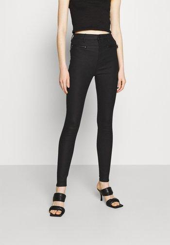 COATED ZIP PANTS - Trousers - black