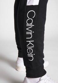 Calvin Klein - LOGO STRIPE  - Tracksuit bottoms - black - 3