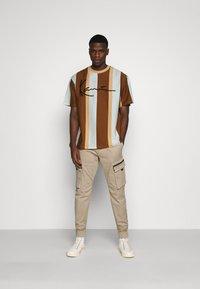 Karl Kani - SIGNATURE STRIPE TEE - Print T-shirt - beige - 1