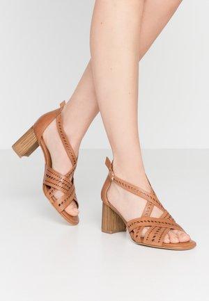 Sandaalit nilkkaremmillä - cognac