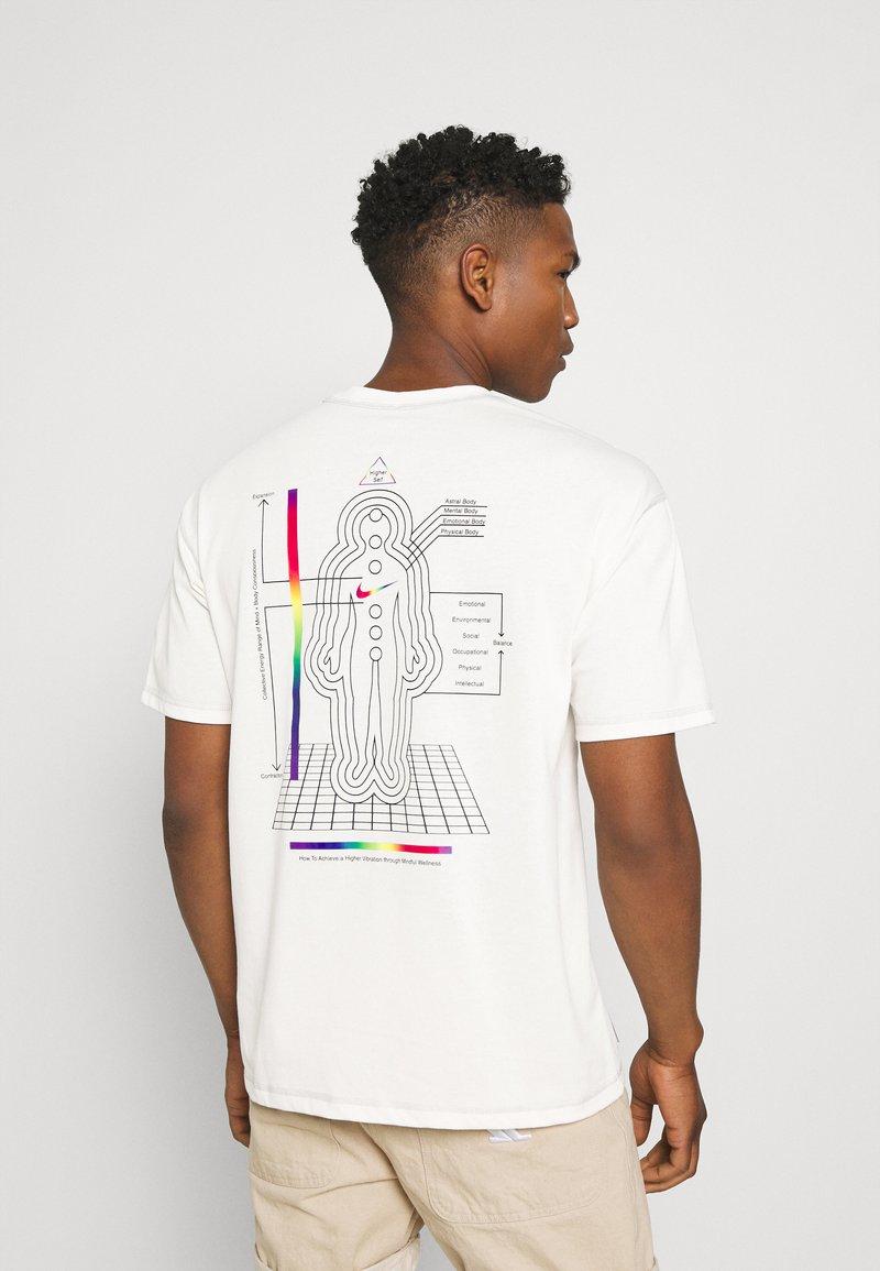 Nike Sportswear - TEE WELLNESS - Print T-shirt - pure