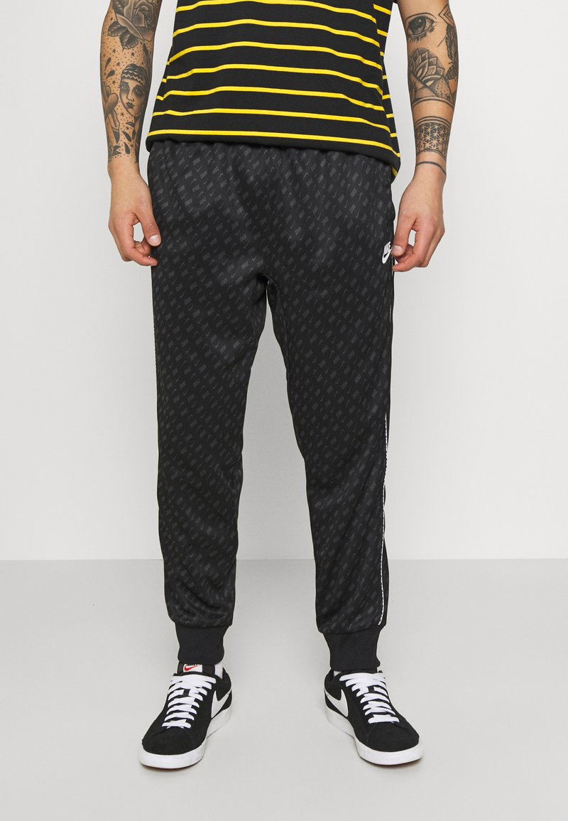Nike Sportswear - REPEAT - Tracksuit bottoms - black/white