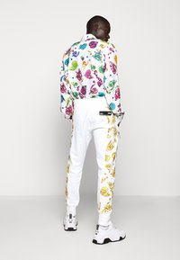 Versace Jeans Couture - JOGGERS GIOIELLI SIDE STRIPE - Tracksuit bottoms - white - 2