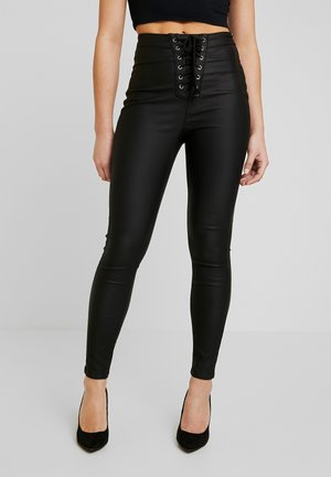 VICE COATED  - Trousers - black