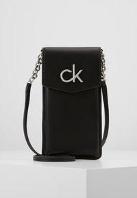 Calvin Klein - RE LOCK PHONE POUCH - Taška spříčným popruhem - black - 0