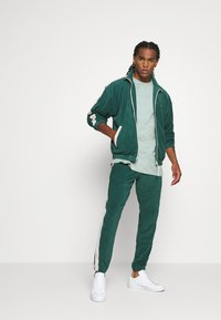 WRSTBHVR - TRACKPANTS LOUNGIN - Tracksuit bottoms - green/off white - 1