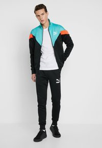 Puma - ICONIC TRACK PANT CUFF - Tracksuit bottoms - black - 1