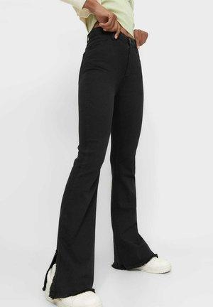 MIT SEITLICHEM SCHLITZ - Bootcut jeans - black