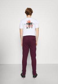 Nominal - CHECK TAPE  - Tracksuit bottoms - burgundy - 2