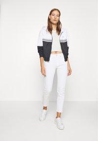Calvin Klein Jeans - STRIPE TAPE HOODED WINDBREAKER - Summer jacket - black - 1