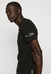 Versace Jeans Couture - TONAL ALLOVER LOGO - T-shirt imprimé - black - 4