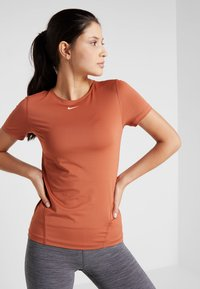 Nike Performance - ALL OVER - Basic T-shirt - dusty peach/echo pink - 0