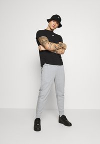 Nike Sportswear - M NSW TCH FLC JGGR - Tracksuit bottoms - grey heather/black